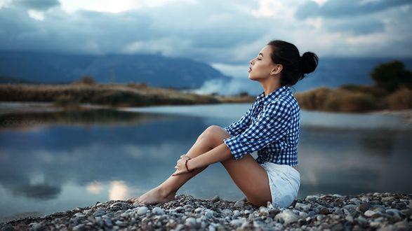 Обои Девушка сидит на каменистом берегу озера