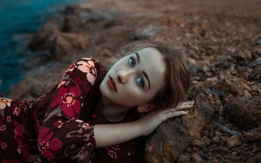 Обои Голубоглазая девушка в цветастом платье лежит на камне на берегу моря