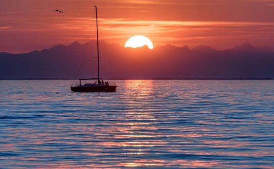 Обои Лодка с людьми на воде на фоне заката