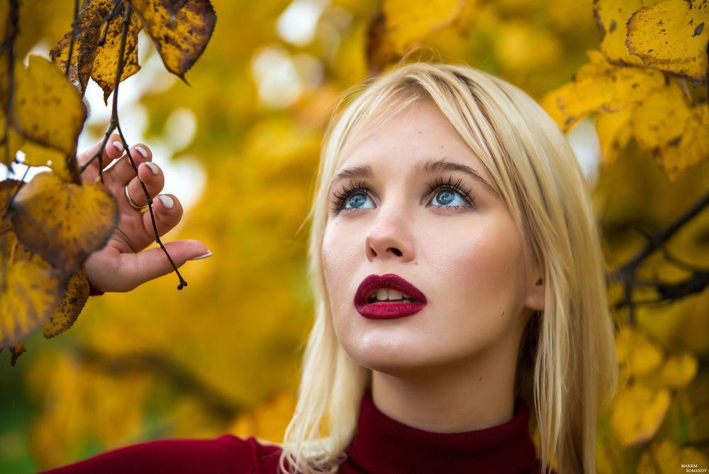 Обои для рабочего стола Девушка держит ветку осеннего дерева и смотрит вверх