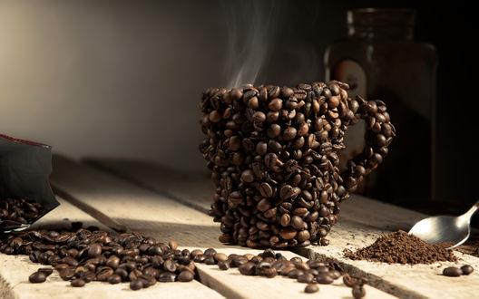 Обои Кофейная чашка из кофейных зерен с кофе, а рядом рассыпанные зерна кофе