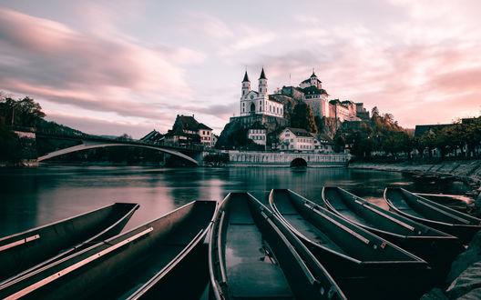 Обои Лодки на берегу озера, вдали виднеется монастырь на холме на фоне предзакатного неба