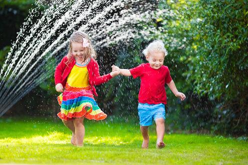 Обои Дети, взявшись за руки, весело убегают от брызг фонтана