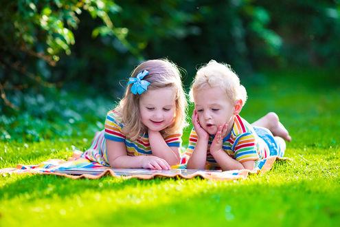 Обои Дети увлеченно разглядывают картинки в книжке, лежа на траве, в тени под деревьями