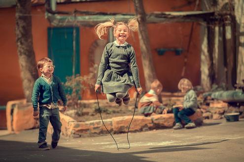 Обои Радостная девочка прыгает на скакалке, а мальчик смотрит на нее, фотограф Марианна Смолина