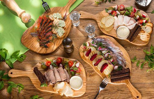 Обои Деревянный стол в летнем саду накрыт богатой закуской - селедкой с картошкой, украшенной свеклой, редисом и луком; салом с черным хлебом, нарезанными помидорами, солеными огурцами и хреном в блюдечке; рядом мясная нарезка, а дальше, пластинки лососины с гренками, намазанными взбитым сливочным маслом с укропом