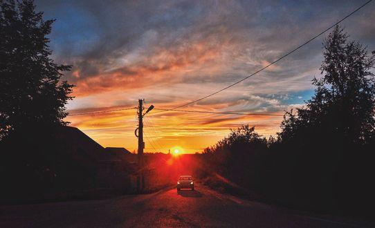 Обои Автомобиль едет по дороге на фоне заката