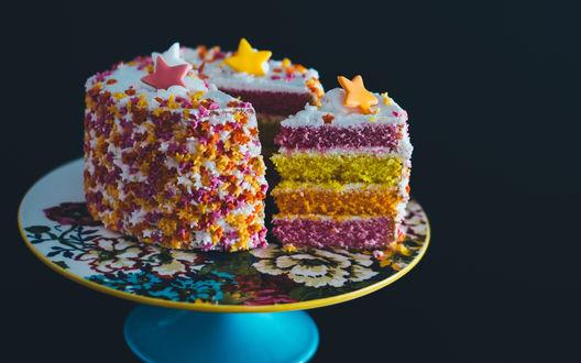 Обои Красочный разноцветный слоеный торт, украшенный звездочками на черном фоне
