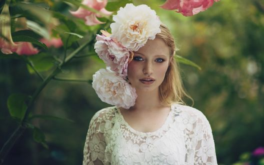 Обои Красивая светловолосая девушка в белом наряде стоит на размытом фоне, а у нее в волосах большие бело-розоватые пионы