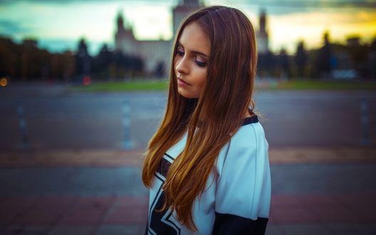 Обои Девушка в спортивной футболке стоит на размытом фоне здания