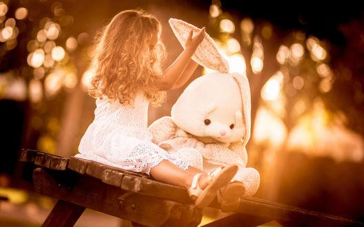 Обои Девочка сидит на лавке с плюшевым зайцем