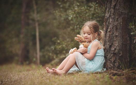 Обои Девочка сидит у дерева и обнимает плюшевого зайца