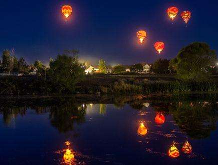 Обои Светящиеся воздушные шары в небе над водоемом