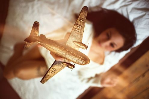 Обои Девушка лежит на постели и держит самолетик