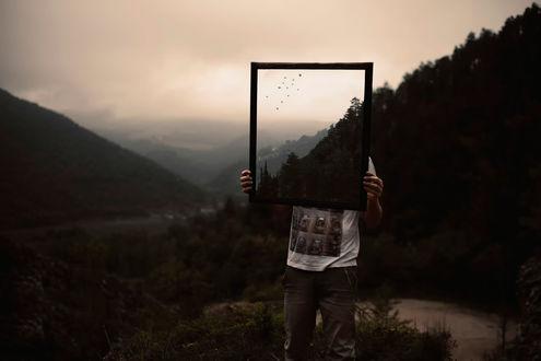Обои Человек с картиной в руках стоит на фоне природы, фотограф Valentino Grassi