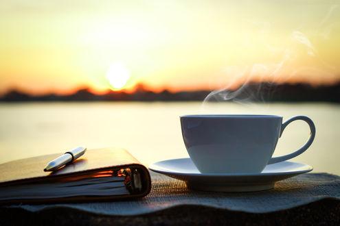 Обои Чашка горячего чая на блюдце, блокнот и ручка на фоне природы