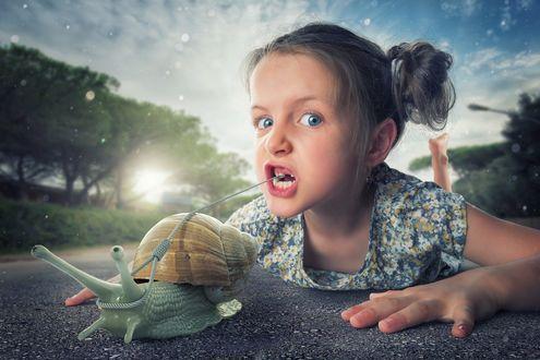 Обои Девочка лежит на дороге перед большой улиткой, которая с помощью веревочки удаляет ей зуб, фотограф John Wilhelm