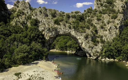 Обои Лодка проплывает под скальной аркой над рекой в лучах летнего солнца, рядом пляж с лодками, Франция