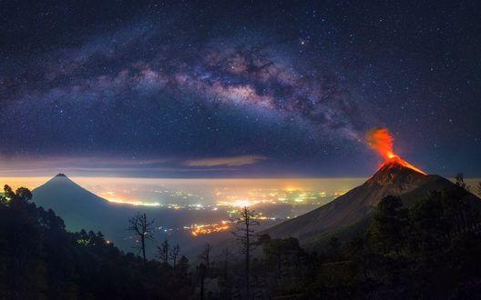 Обои Извержение вулкана в горах Гватемалы на фоне ночного неба и Млечного пути, вдали виднеются огни города, фотограф Albert Dros