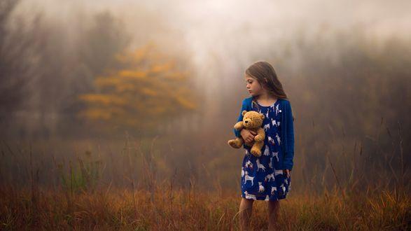 Обои Девочка с плюшевым медвежонком в руках стоит на поляне