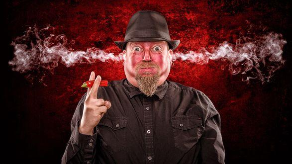 Обои У мужчины в шляпе, который откусил кусочек острого чили перца, идет дым из ушей