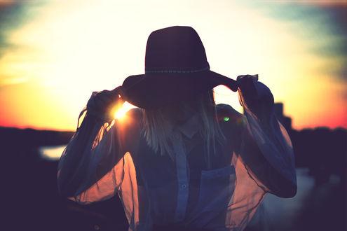 Обои Девушка в прозрачной блузе и шляпе стоит на фоне заката, фотограф Julia Caesar