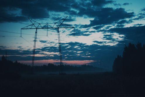 Обои Высоковольтное сооружение с проводами на фоне ночного облачного неба