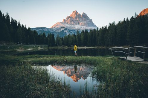 Обои Парень стоит у озера, окруженного лесом, за которым видна гора, фотограф Johannes Hulsch