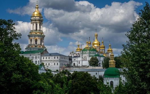Обои Комплекс Киево-Печерской Лавры, Киев, Украина виднеется за деревьями на фоне ярко-голубого неба с бело-серыми тучами