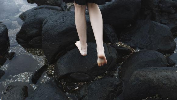 Обои Девушка идет по мокрым черным камням у воды