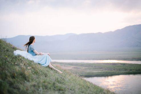 Обои Девушка в голубом платье сидит на склоне у реки на рассвете