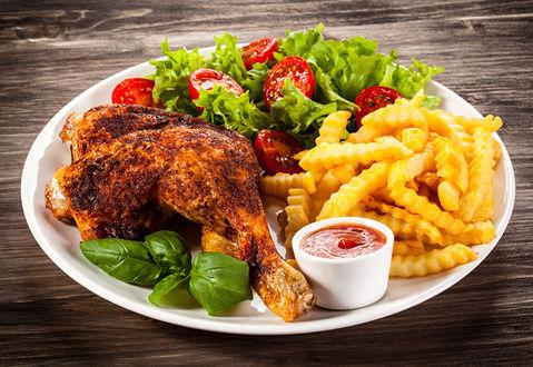 Обои Аппетитно зажаренная куриная ножка рядом с листьями салата и базилика, картошкой фри и помидорками черри, там же плошка с кетчупом
