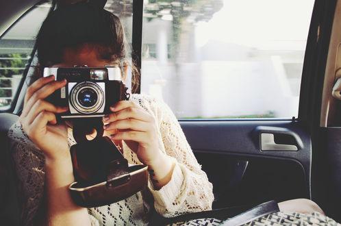 Обои Девушка с фотоаппаратом сидит в машине, автор Andrea Cisneros