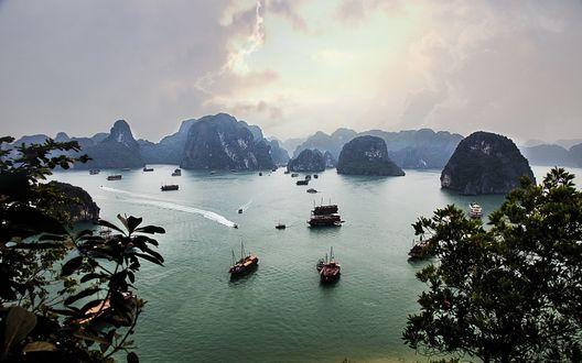 Обои Корабли в бухте Halong Bay, Vietnam / Вьетнам на фоне скал в море и неба, затянутого дымкой
