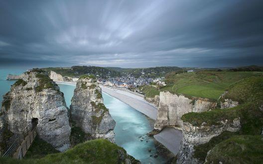 Обои Небольшая бухта среди скал на побережье Нормандии, Франция, на фоне неба, затянутого серыми тучами