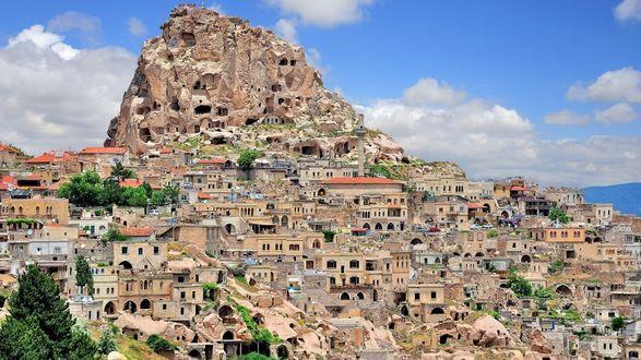 Обои Город, раскинувшийся террасами у подножья гор, над ним скалы, в которых разместился старинный скальный город, Каппадокия, Турция на фоне голубого неба с белыми тучками
