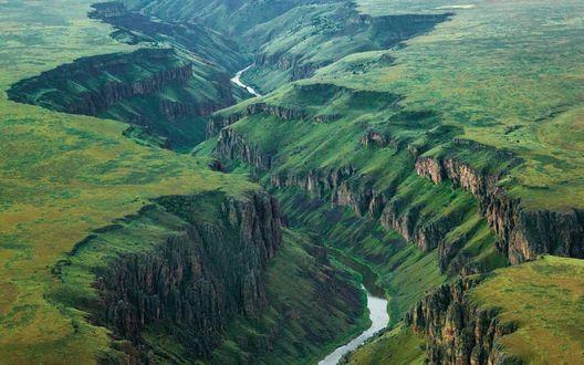 Обои Река змеится на дне расщелины посреди зеленого плато