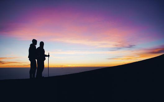 Обои Силуэты двух туристов стоят у подножья горы на фоне заката и сгущающейся темноты
