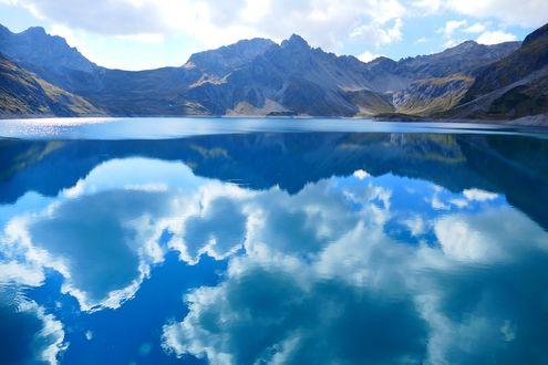Обои Голубое облачное небо отражается в озере, окруженном горами