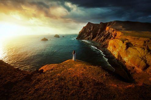 Обои Девушка в длинном платье стоит на обрыве перед синим морем, фотограф TJ Drysdale