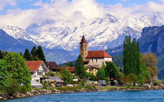 Обои Небольшое поселение с красивыми домиками возле горного озера на фоне заснеженных вершин и белых облаков