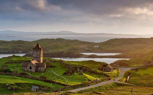 Обои Небольшой замок с башенкой и домиками, извилистая дорога, небольшое озеро среди зеленых холмов Шотландии на фоне затянутого тучами неба
