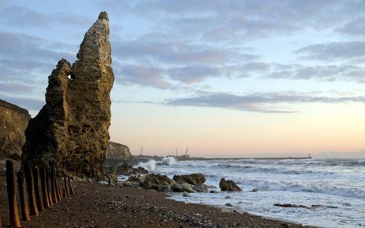 Обои Известняковые скалы на морском берегу на фоне шторма и затянутого тучами неба