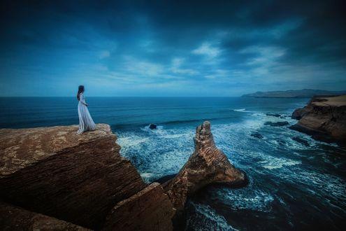 Обои Девушка стоит на обрыве на фоне волнующегося моря, фотограф TJ Drysdale