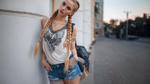 Обои Девушка в шортах и футболке стоит у стены дома