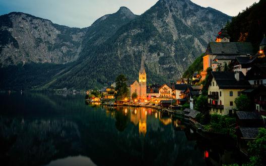 Обои Освещенная вечерним солнцем деревушка у подножия гор на берегу горного озера, Halstatt, Австрия