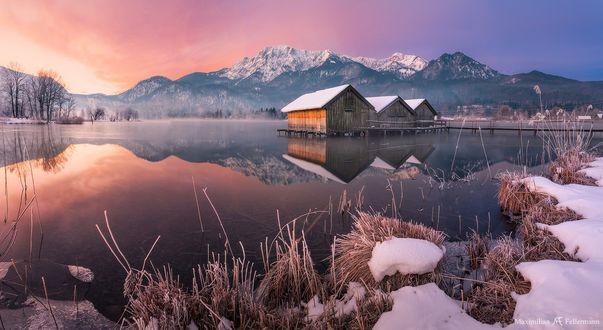 Обои Дома стоят на сваях в озере у заснеженных гор