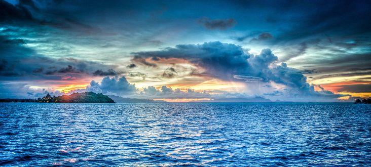 Обои Высокое облачное небо над ярко-синей морской водой