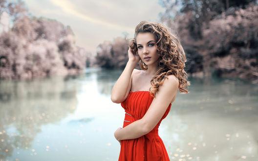 Обои Красивая девушка с вьющимися волосами в красном платье на фоне пруда в размытых тонах, фотограф Alessandro Di Cicco