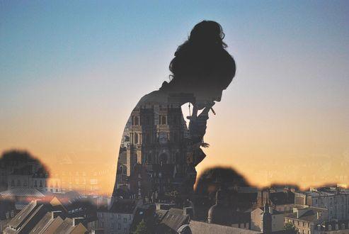 Обои Силуэт курящей девушки на фоне города
